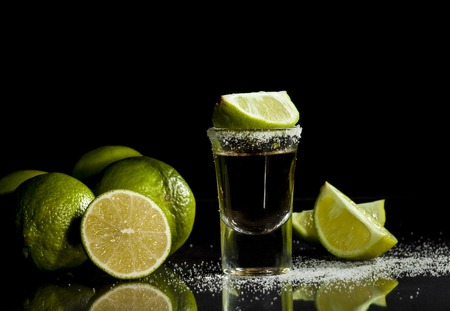 mexican black: Gold tequila shot with lime fruits isolated on white background