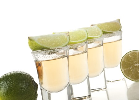 lime green background: Gold tequila shots with lime fruits isolated on white background
