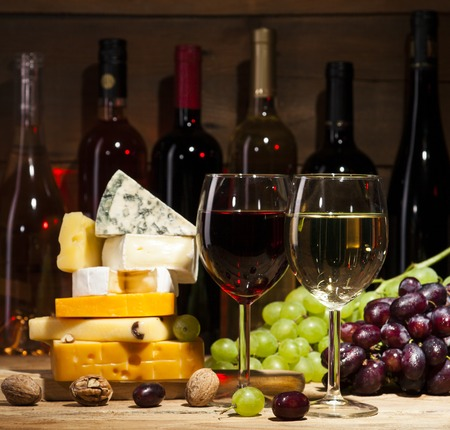 Refined still life of wine, cheese, walnuts, grapes on old wooden beige background