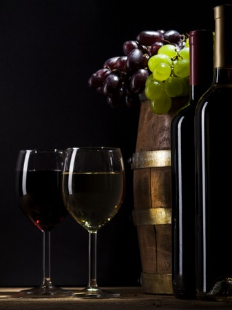 Still life with wine, bunch of grapes and wooden barrel on black background