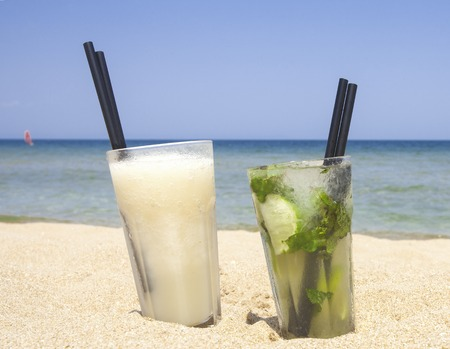 Glasses of fresh mojito and banana daiquiri cocktails on the beach