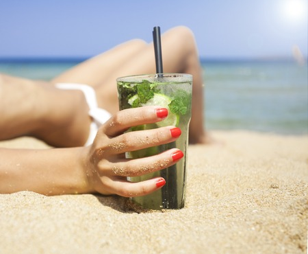 liquor girl: Woman holding glass of fresh mojito cocktail on the beach Stock Photo