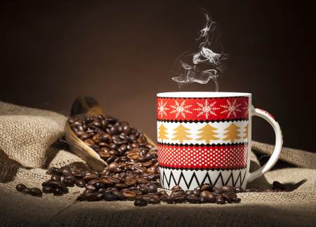 Christmas coffee cup and coffee beans on burlap textile and brown background.