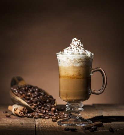 Transparent  glass coffee cup and wooden spoon with coffee beans on wooden and brown background.