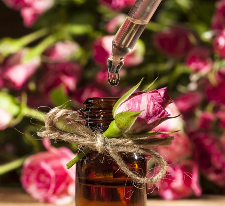 Closeup of bottle with rose essential oil on wooden background.