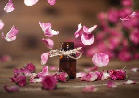 Closeup of bottle with rose essential oil with falling leaves on wooden background.