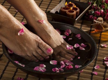 Pieds féminins avec des gouttes d'eau, bol de spa, des serviettes, des fleurs et des bougies. Banque d'images - 46949220