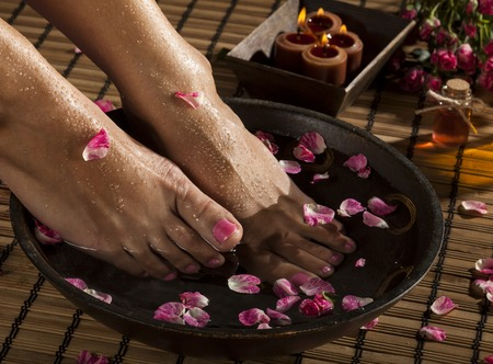 Female feet with drops of water, spa bowl, towels, flowers and candles.