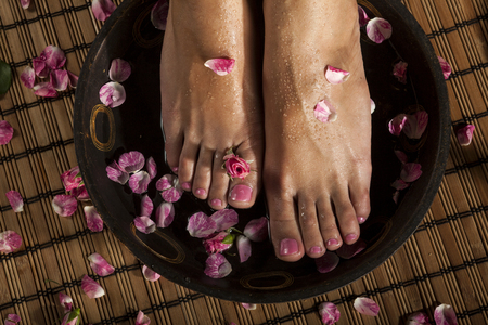 woman bath: Female feet with drops of water in spa bowl with water and roses.