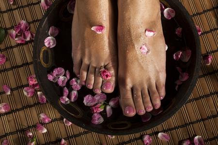 Pies femeninos con gotas de agua en un tazón de hidromasaje con agua y rosas.