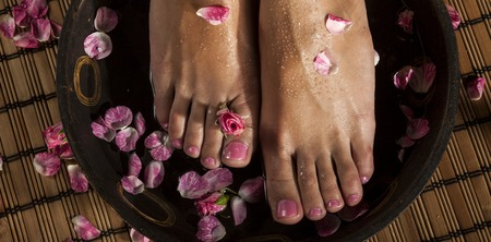 spa flower: Female feet with drops of water in spa bowl with water and roses.