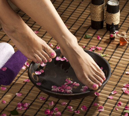 easing: Female feet with spa bowl, towels, flowers and candles.