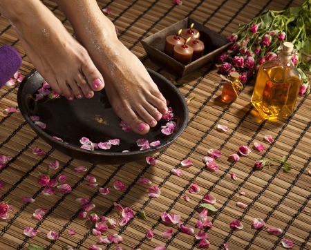 footcare: Female feet with drops of water, spa bowl, towels, flowers and candles.