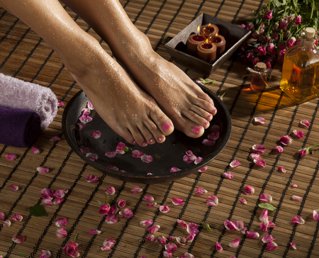 easing: Female feet with drops of water, spa bowl, towels, flowers and candles.