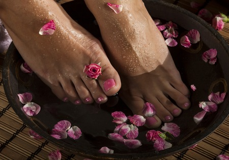 woman in bath: Female feet with drops of water in spa bowl with water and roses.