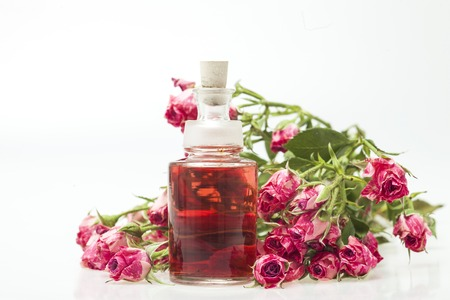 Closeup of bottle with rose essential oil on white background.