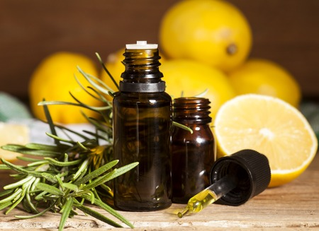 Lemon essential oil, lemon fruit and rosemary on wooden background