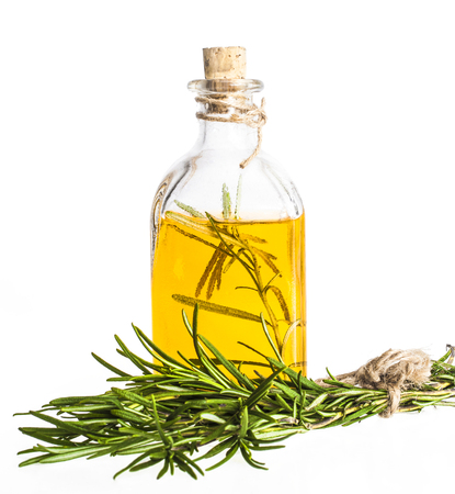 Essential oil with rosemary flowers on white background