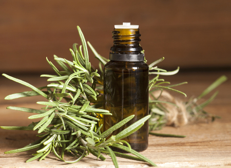 alternative living: Essential oil with rosemary flowers on wooden background Stock Photo