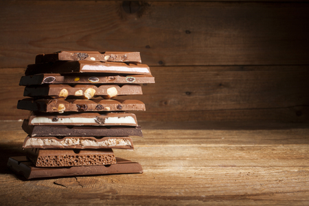 Chocolate blocks stack with different kind of chocolate on wooden background