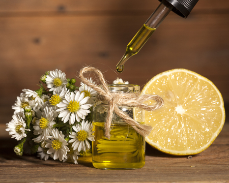 Lemon and chamomile essential oil on wooden background Banque d'images