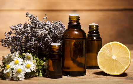 Chamomile, lemon and lavender essential oil on wooden background