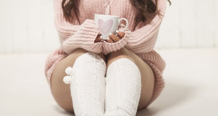 Girl with warm socks and sweater sitting on the floor with cup of coffee, hot chocolate or tea. Stock Photo