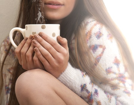 Girl with warm brown boots and sweater sitting on the floor with cup of coffee, hot chocolate or tea.