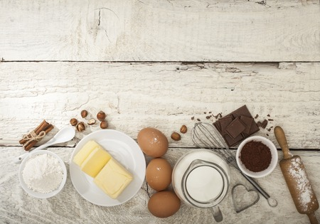 Ingredients for the preparation of bakery products: flour eggs butter milk chocolate cocoa nuts. Top view. Rustic style. White wooden background. Foto de archivo