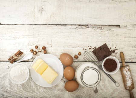 mleka: Ingredients for the preparation of bakery products: flour eggs butter milk chocolate cocoa nuts. Top view. Rustic style. White wooden background. Zdjęcie Seryjne