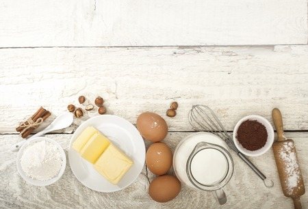 Ingredients for the preparation of bakery products: flour eggs butter milk cocoa nuts. Top view. Rustic style. White wooden background.