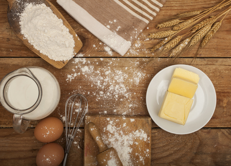 milk and cookies: Ingredients for the preparation of bakery products: flour eggs butter milk wheat spikes. Top view. Rustic style. Brown wooden background.