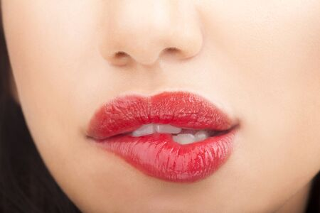Woman who bites his lips whith red lipstick