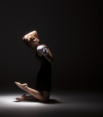 Modern female dancer dancing with face mask on dark background. Conceptual photo