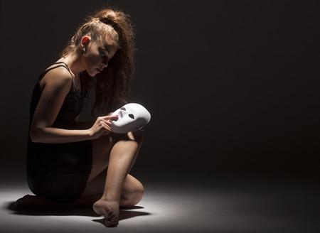 현대 여성 댄서 어두운 배경에 얼굴 마스크와 춤. 개념적 사진