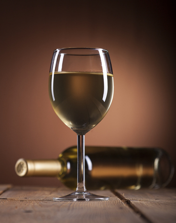 muscadet: Wineglass and bottle with white wine on wooden background Stock Photo