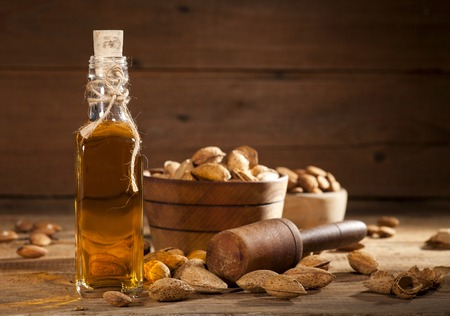 Almond oil and nuts on an old wooden background, selective focus Banque d'images
