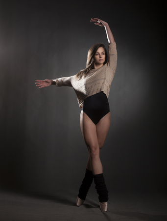 leotard: Young beautiful dancer in beige sweater and black leotard posing on a gray studio background