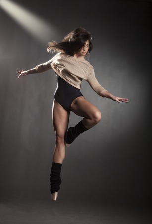 turnanzug: Junge schöne Tänzerin in beige Pullover und schwarzen Anzug posiert auf einem grauen Hintergrund Studio