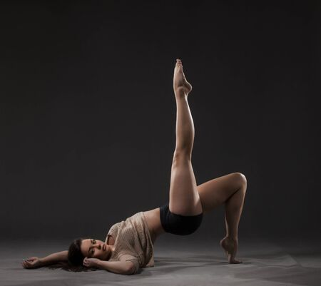 short pants: Young beautiful dancer in beige sweater and black short pants posing on a gray studio background