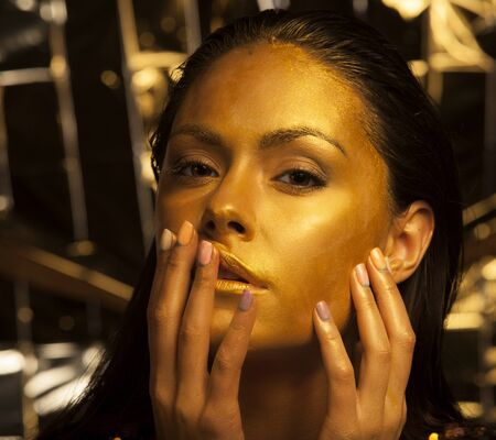 bodyart: Portrait of beautiful woman with golden makeup and bodyart