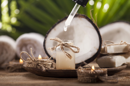 Coconuts and coconut oil on wooden table, on nature background. Health spa background. Banque d'images