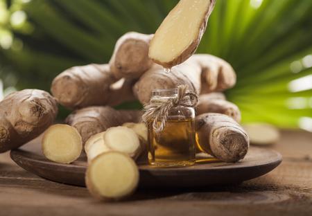 Öl von Ingwer in einer kleinen Glasflasche Makro und Wurzel auf tropische Blätter Hintergrund