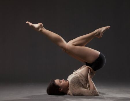 black sweater: Young beautiful dancer in beige sweater and black leotard posing on a gray studio background
