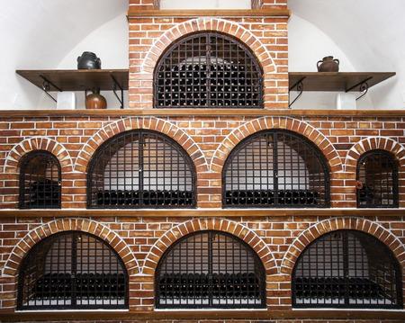 maturing: Old bottles of wine maturing in a wine cellar brick vault