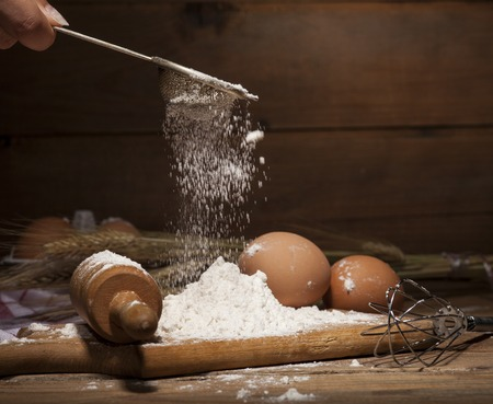 Ingredients for the preparation of bakery products - milk, eggs, butter, flour - on rustic wooden background. Stock Photo
