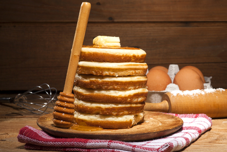 drizzler: A tall stack of pancakes with dripping honey from drizzler and butter on wooden background.