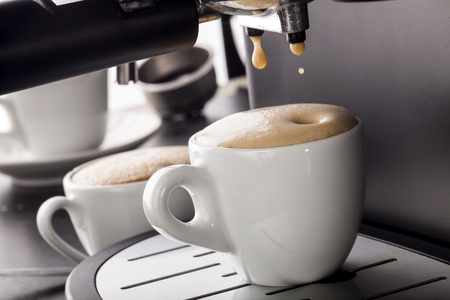 Close-up of espresso pouring from coffee machine in a white cup Banque d'images
