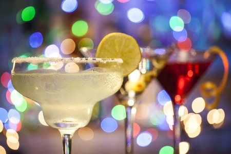 sweet vermouth: Glasses of margarita, martini and cosmopolitan cocktails on bar lights background with copy space