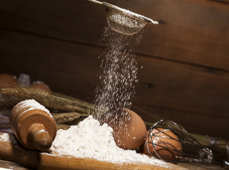Ingredients for the preparation of bakery products - milk, eggs, butter, flour - on rustic wooden background. Banque d'images
